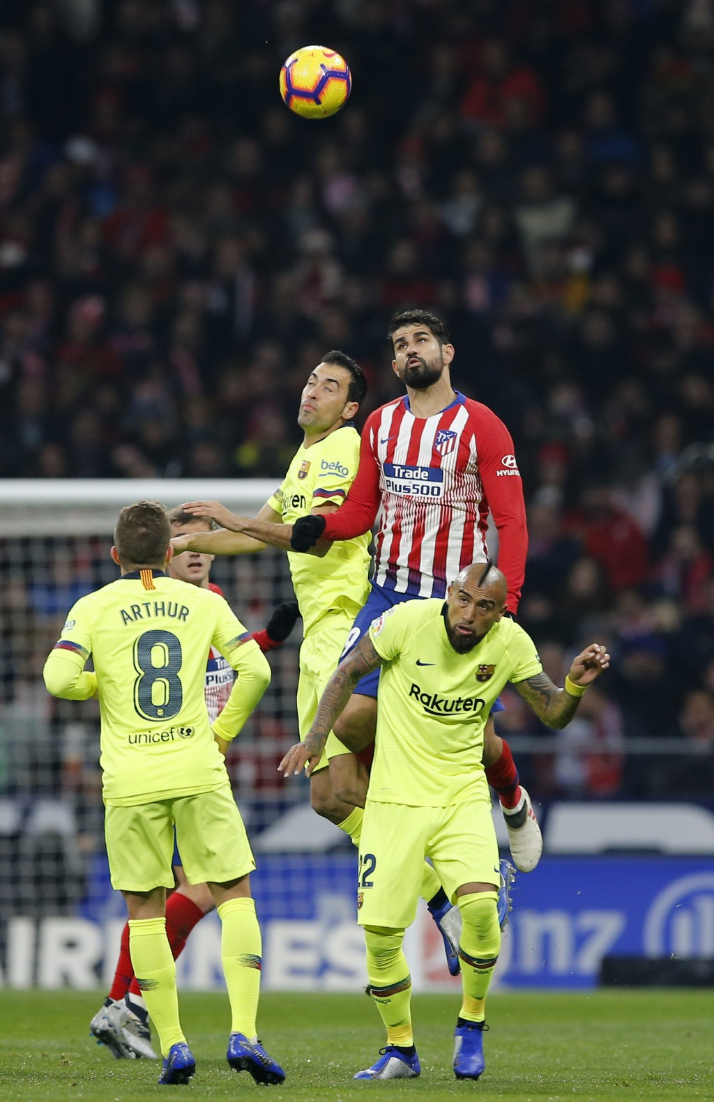 Atletico's Diego Costa, right, jumps for the ball with Barcelona's Sergio Busquets during a Spanish La Liga soccer match between Atletico Madrid and F