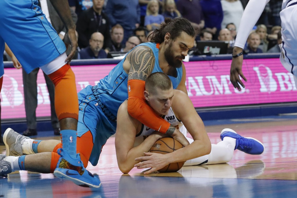 Oklahoma City Thunder center Steven Adams, top, and Denver Nuggets forward Mason Plumlee, bottom, compete for a loose ball during the first half of an