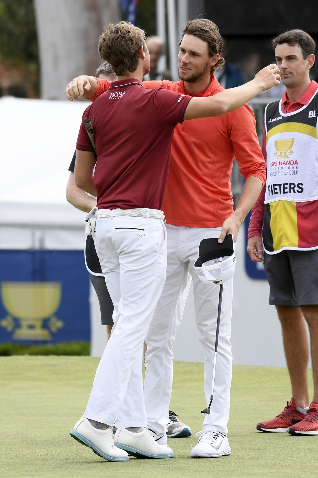 Belgium's Thomas Detry, left, and Thomas Pieters hug each other on the 18th green after winning the World Cup of Golf in Melbourne, Australia, Sunday,...