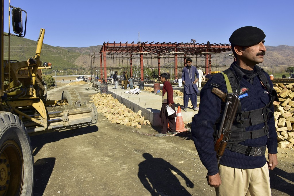 FILE - In this Dec. 22, 2017 file photo, a Pakistani police officer stands guard at the site of Pakistan China Silk Road in Haripur, Pakistan. The ass...