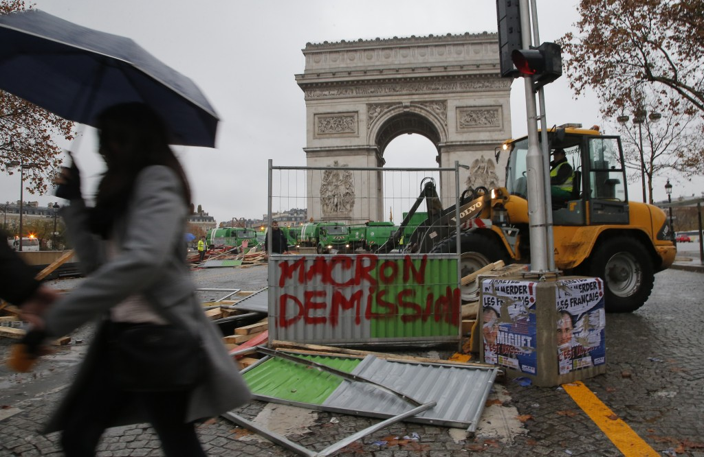 A bulldozer cleans the street from a barricade in the aftermath of a protest against the rising of the fuel taxes at the Champs Elysees avenue in Pari...