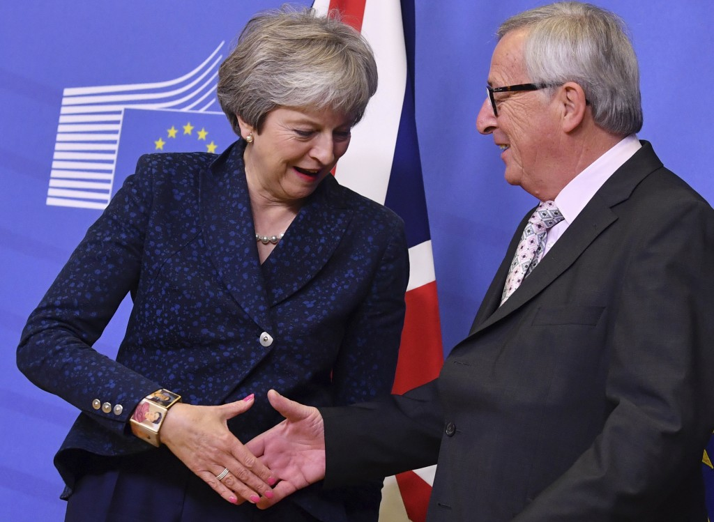 European Commission President Jean-Claude Juncker, right, shakes hands with British Prime Minister Theresa May prior to a meeting at EU headquarters i...
