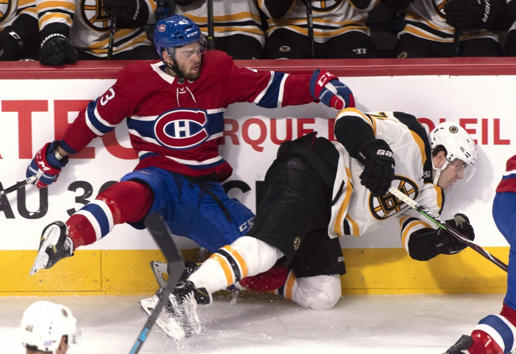 Montreal Canadiens' Michael Chaput and Boston Bruins' Jake DeBrusk meet along the boards during the first period of an NHL hockey game Saturday, Nov.