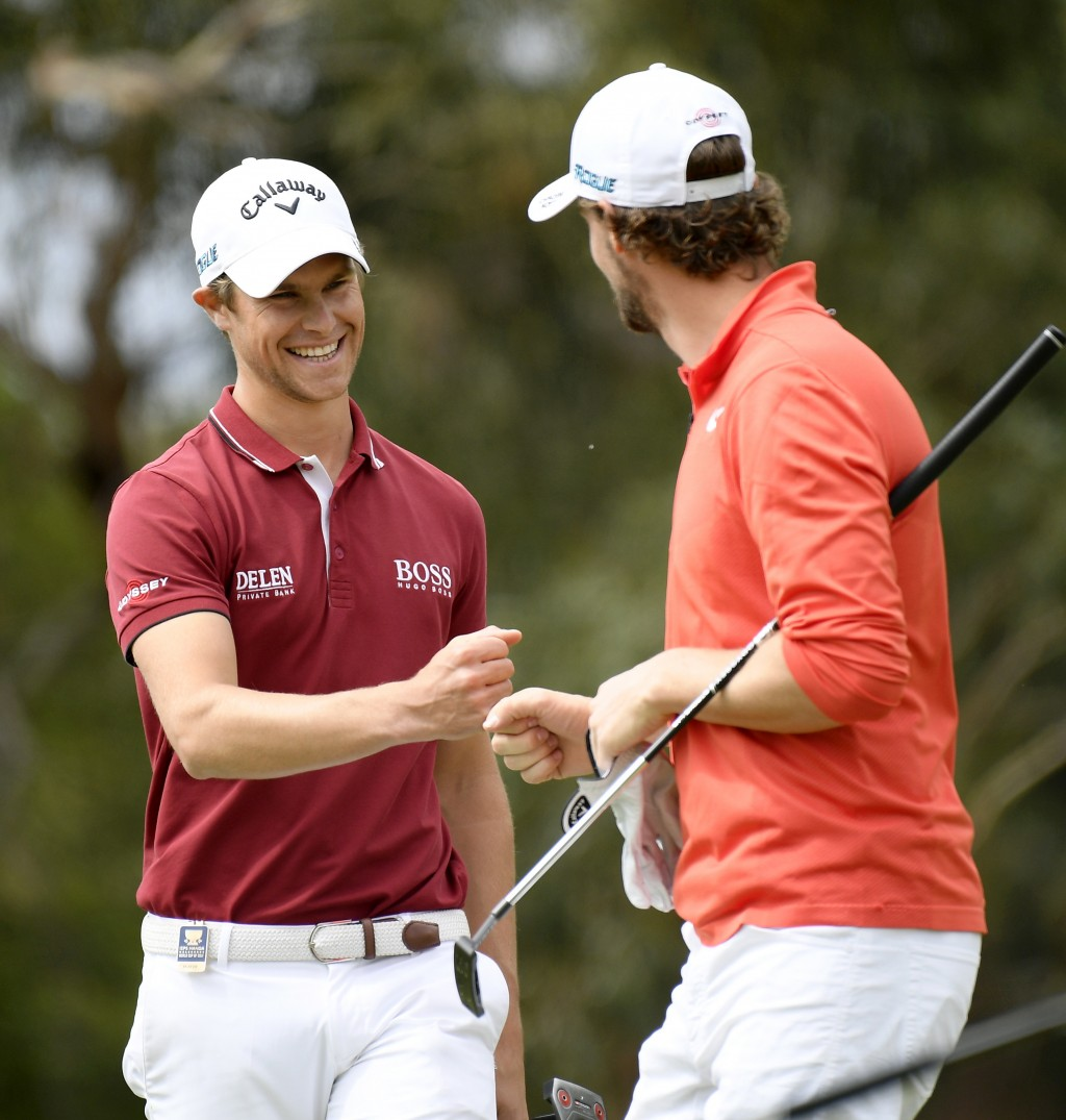 Belgium's Thomas Detry, left, and Thomas Pieters congratulate each other after winning the World Cup of Golf in Melbourne, Australia, Sunday, Nov. 25,