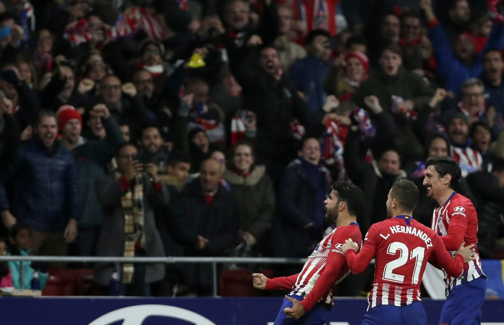 Athletico Madrid's Diego Costa, left, celebrates with teammates after scoring his side's opening goal during a Spanish La Liga soccer match between At