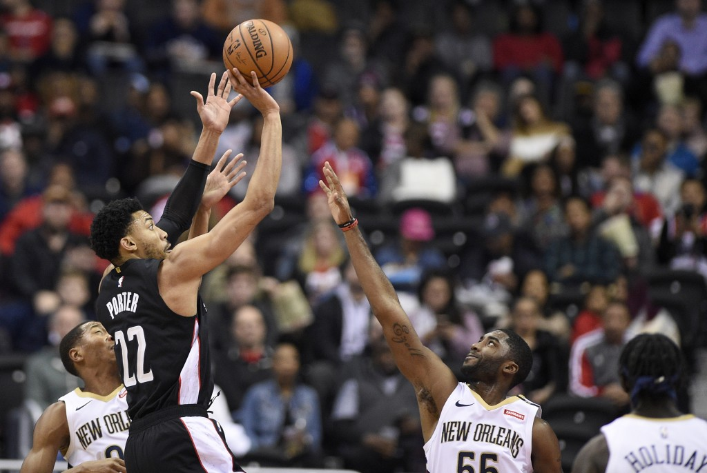 Washington Wizards forward Otto Porter Jr. (22) shoots against New Orleans Pelicans guard E'Twaun Moore (55) and guard Jrue Holiday, right, during the