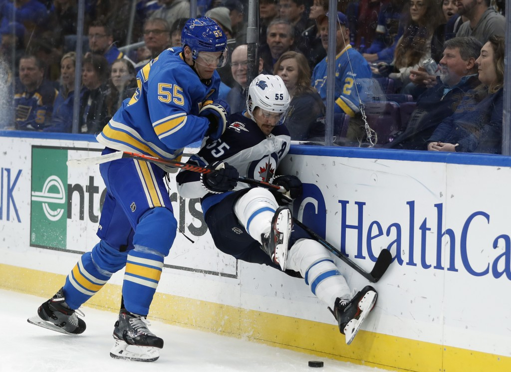 Winnipeg Jets' Mark Scheifele, right, is checked into the boards by St. Louis Blues' Colton Parayko during the first period of an NHL hockey game Satu...