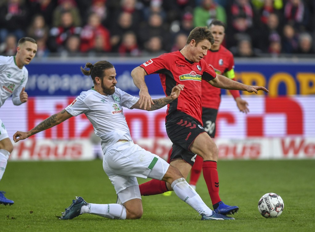 Freiburg's Dominique Heintz, right, and Bremen's Martin Harnik, left, challenge for the ball during the German Bundesliga soccer match between SC Frei...