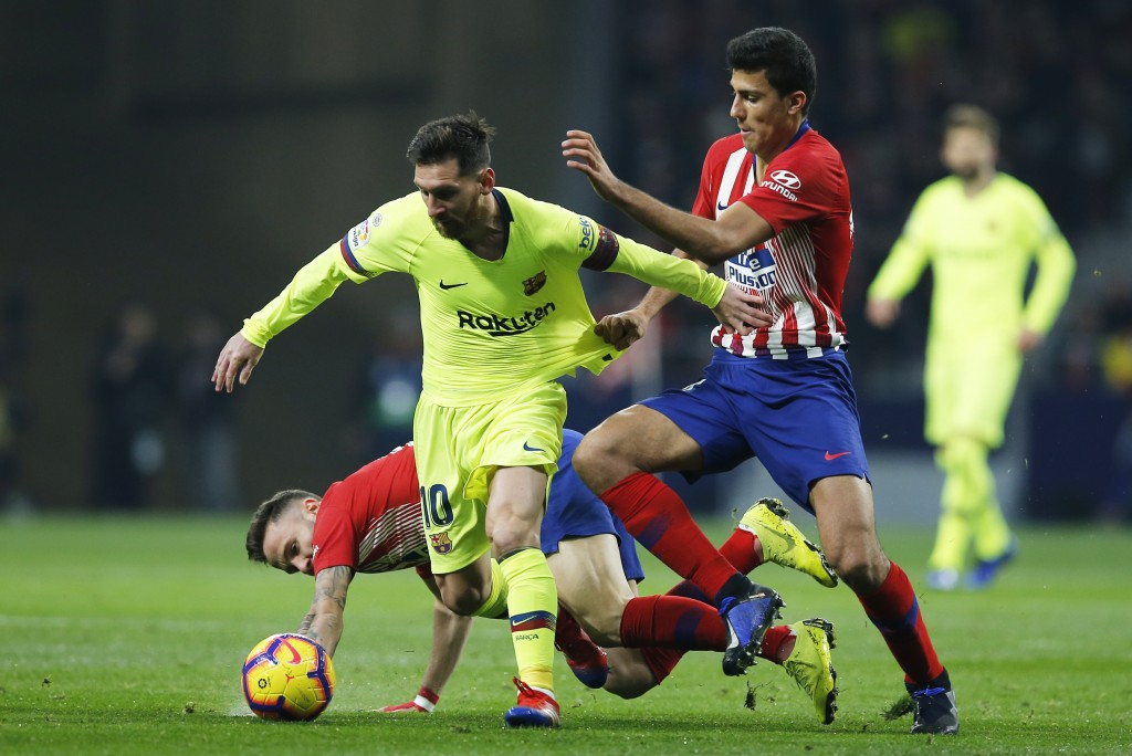 Atletico's Rodrigo Hernandez, right, grabs Barcelona's Lionel Messi by the shirt during a Spanish La Liga soccer match between Atletico Madrid and FC