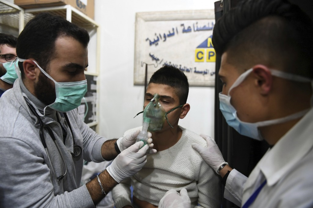 In this photo released by the Syrian official news agency SANA, shows a man receiving oxygen through respirators following a suspected chemical attack