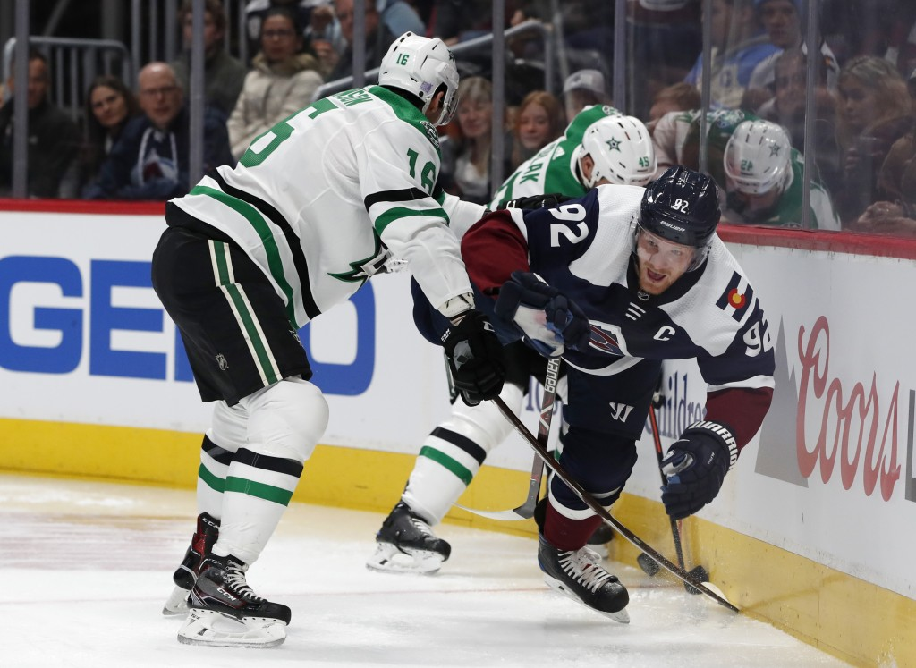 Dallas Stars center Jason Dickinson, left, flips Colorado Avalanche left wing Gabriel Landeskog off his skates as he tries to control the puck in the