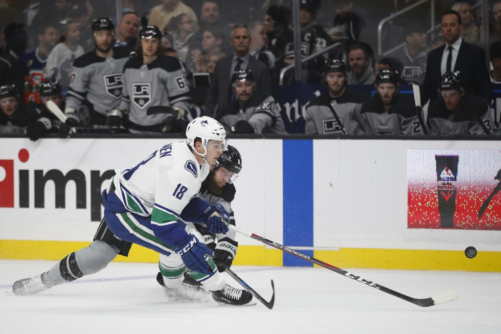 Vancouver Canucks' Jake Virtanen, front, and Los Angeles Kings' Jake Muzzin chase the puck during the first period of an NHL hockey game Saturday, Nov