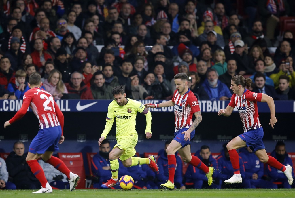 Barcelona's Lionel Messi, 2nd left, runs with the ball during a Spanish La Liga soccer match between Atletico Madrid and FC Barcelona at the Metropoli