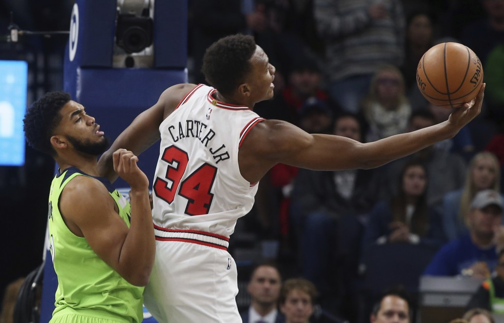 Chicago Bulls' Wendell Carter Jr., right, reaches to catch the ball as Minnesota Timberwolves' Karl-Anthony Towns defends in the first half of an NBA