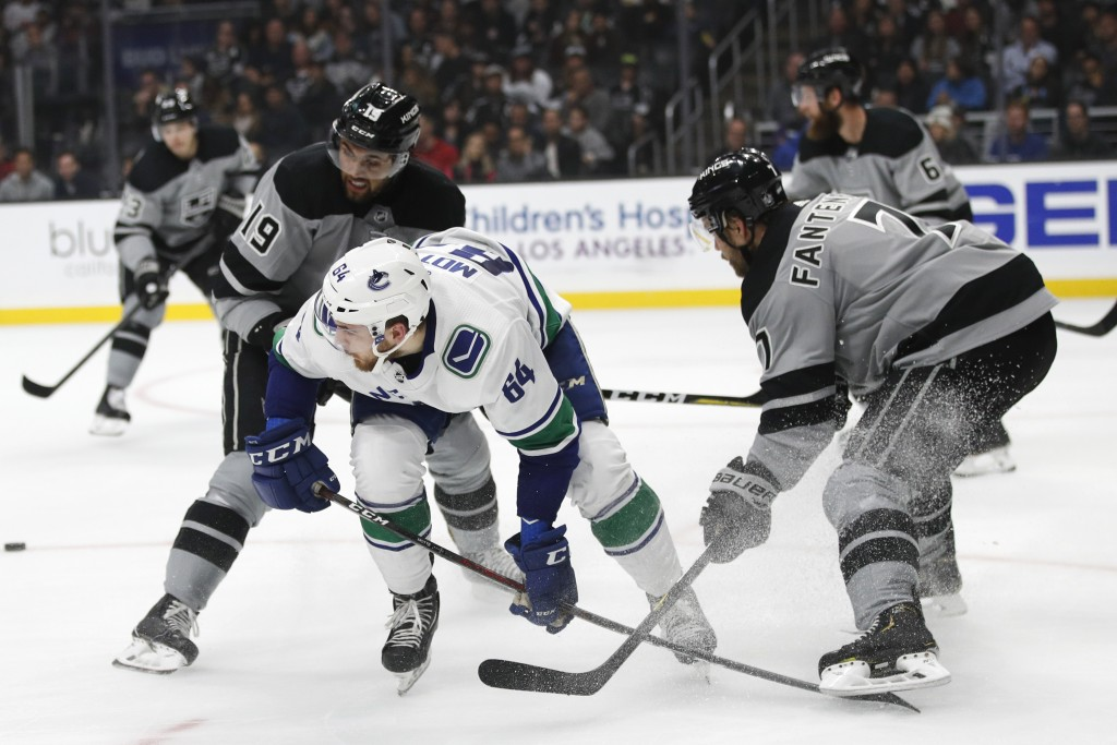 Vancouver Canucks' Tyler Motte, center, is pressured by Los Angeles Kings' Oscar Fantenberg, right, of Sweden, and Alex Iafallo during the first perio