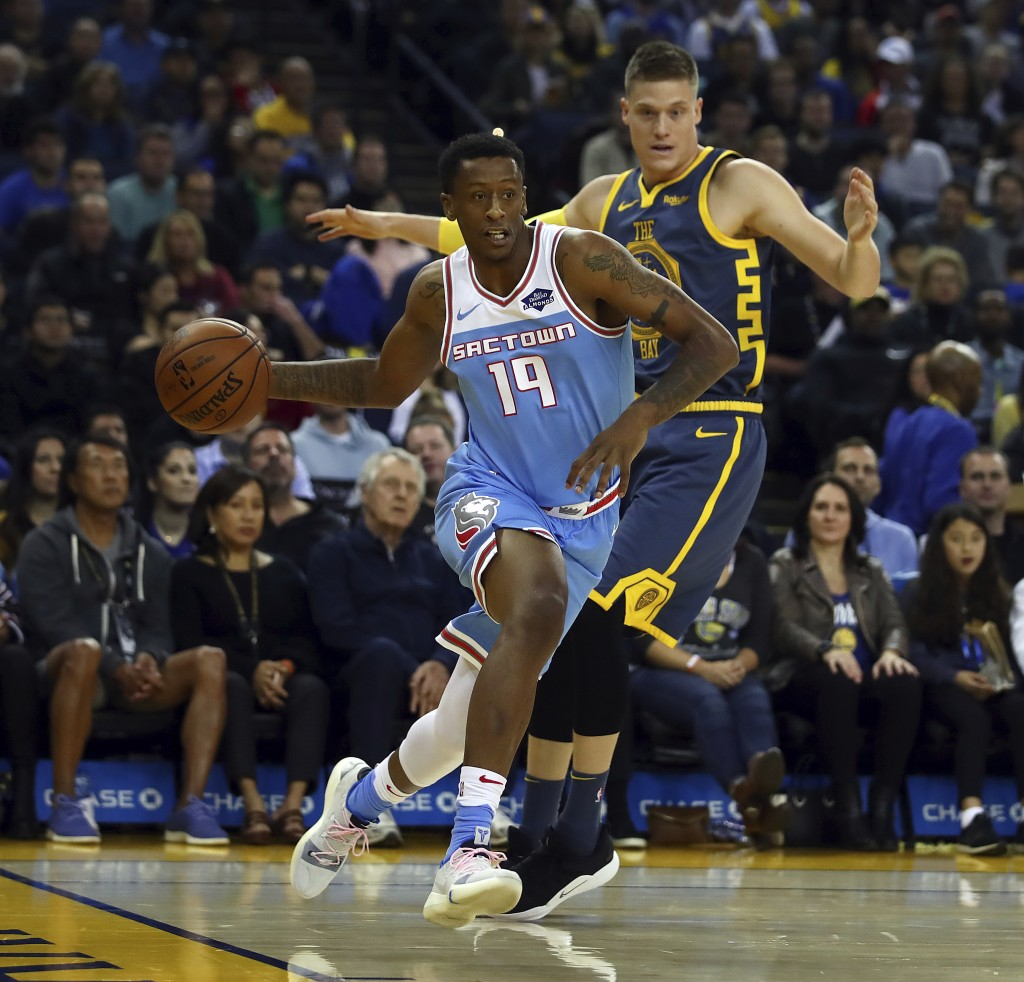 Sacramento Kings' Troy Williams, left, drives the ball past Golden State Warriors' Jonas Jerebko during the first half of an NBA basketball game Satur