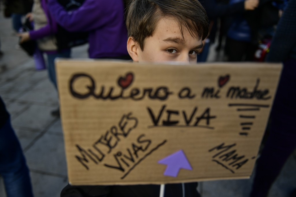 A young boy holds banner reading, ''living women, I want my mother alive'' while protesting male violence against women, in Pamplona, northern Spain, ...