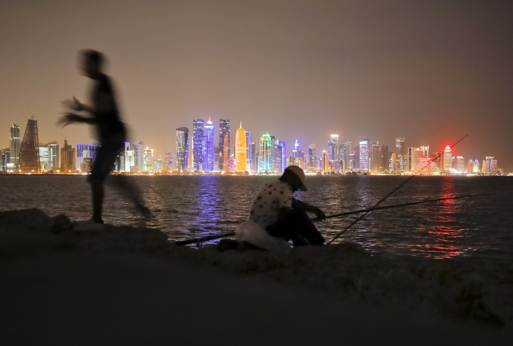 In this Nov. 2, 2018 picture men fish, backdropped by the city skyline Doha, Qatar. Eight stadiums scattered in a 30-mile radius that will host 32 tea