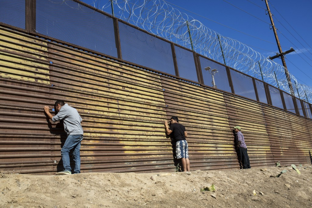 Migrants peer through the border wall after pushing past Mexican police at the Chaparral crossing in Tijuana, Mexico, Sunday, Nov. 25, 2018, as they t...