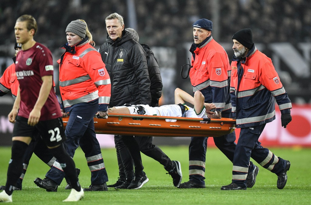 Moenchengladbach's Matthias Ginter is carried from the pitch injured during the German Bundesliga soccer match between Borussia Moenchengladbach and H...