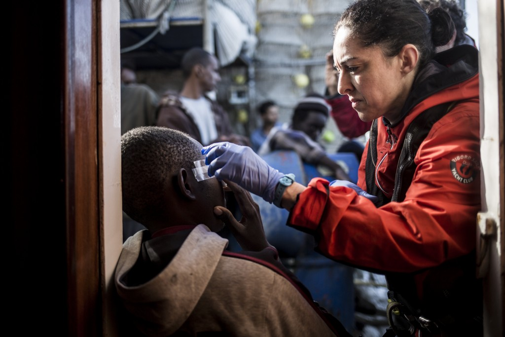 In this photo taken on Saturday, Nov. 24, 2018 photo, a migrant receives medical assistance after being rescued by Nuestra Madre de Loreto, a Spanish ...