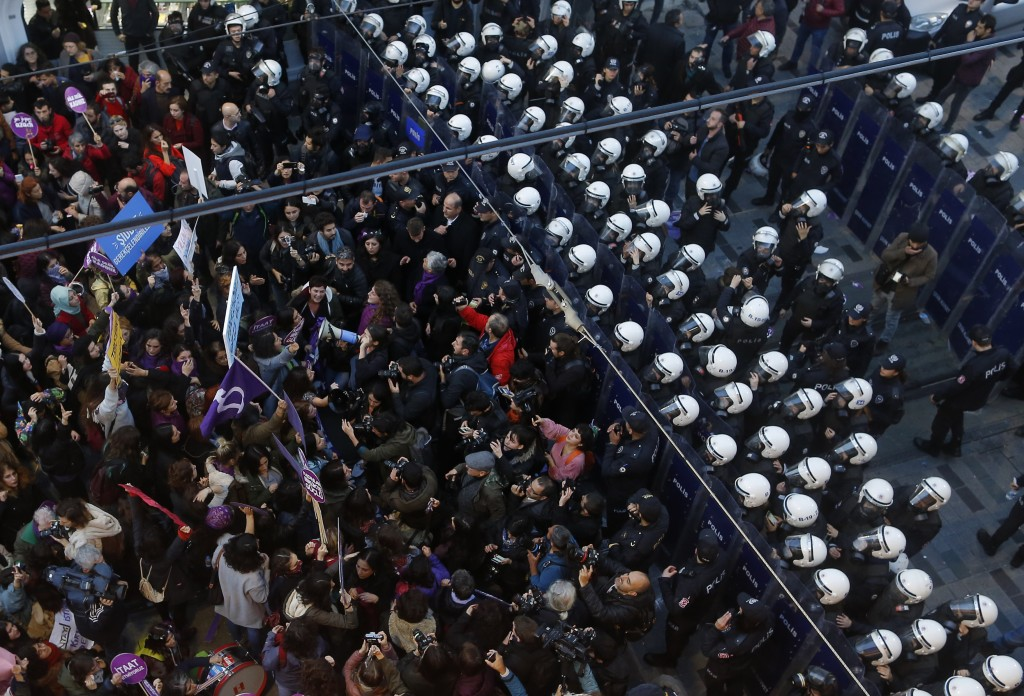 A Phalanx of Turkish police officers in riot gear, right, block protesters during a rally in central Istanbul's Istiklal Avenue, the main shopping roa