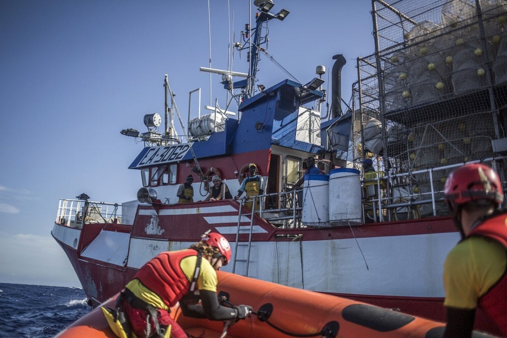 In this photo taken on Saturday, Nov. 24, 2018 photo, Members of Spanish NGO Proactiva Open Arms approach Nuestra Madre de Loreto, a Spanish fishing v