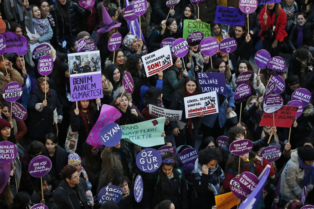 Protesters, mostly women, display various placards calling to end violence towards women, and chant slogans during a rally in central Istanbul, Sunday...