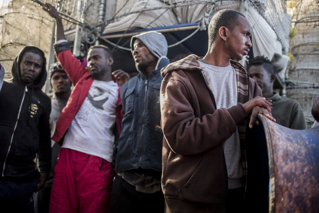 In this photo taken on Saturday, Nov. 24, 2018 photo, Migrants from Somalia, Nigeria, Sudan, Senegal and Egypt stand on the deck of Nuestra Madre de L