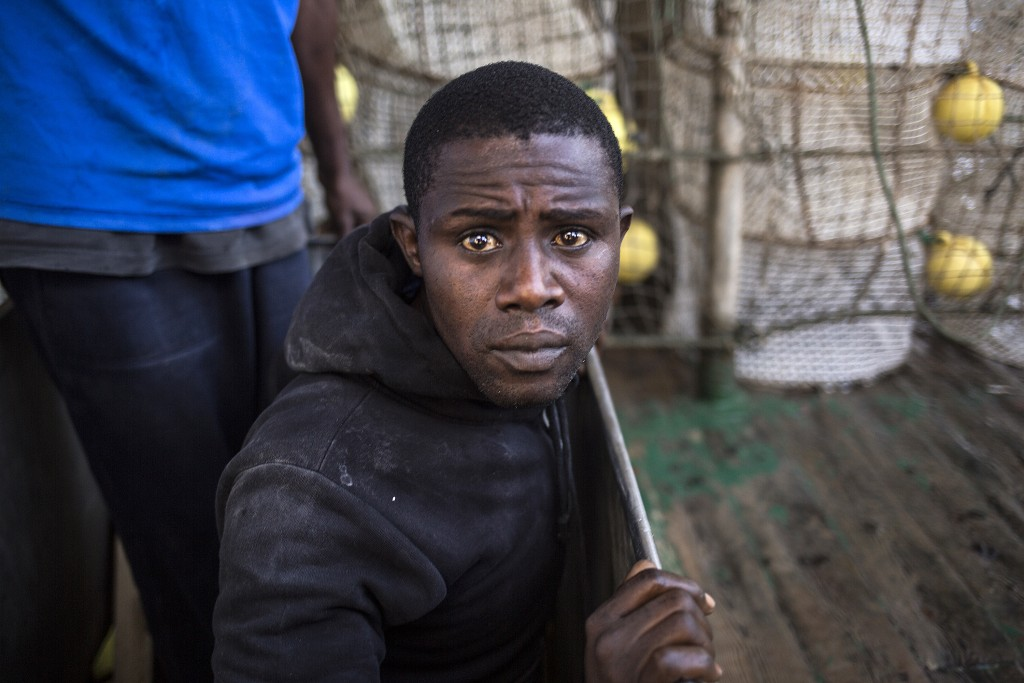 In this photo taken on Saturday, Nov. 24, 2018 photo, a migrant rests aboard Nuestra Madre de Loreto, a Spanish fishing vessel that rescued twelve mig...