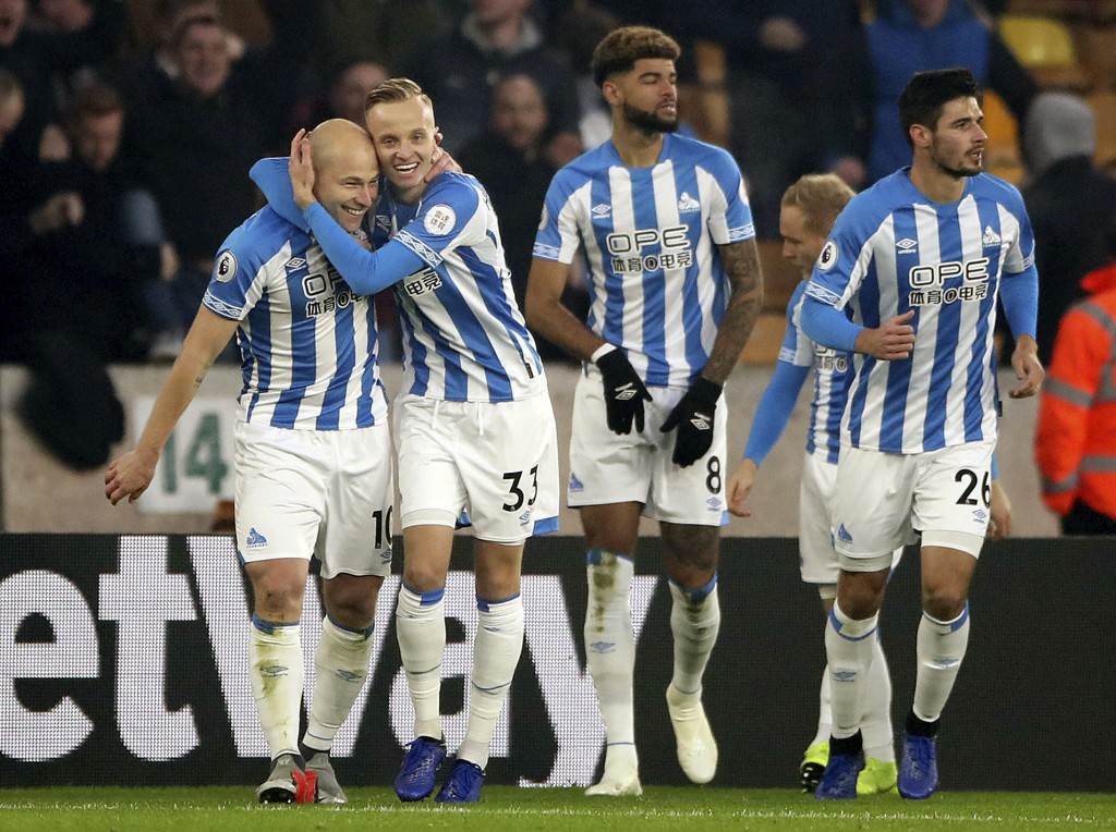 Huddersfield's Aaron Mooy, left, celebrates with teammate Florent Hadergjonaj after scoring his side's first goal during a Premier League soccer match