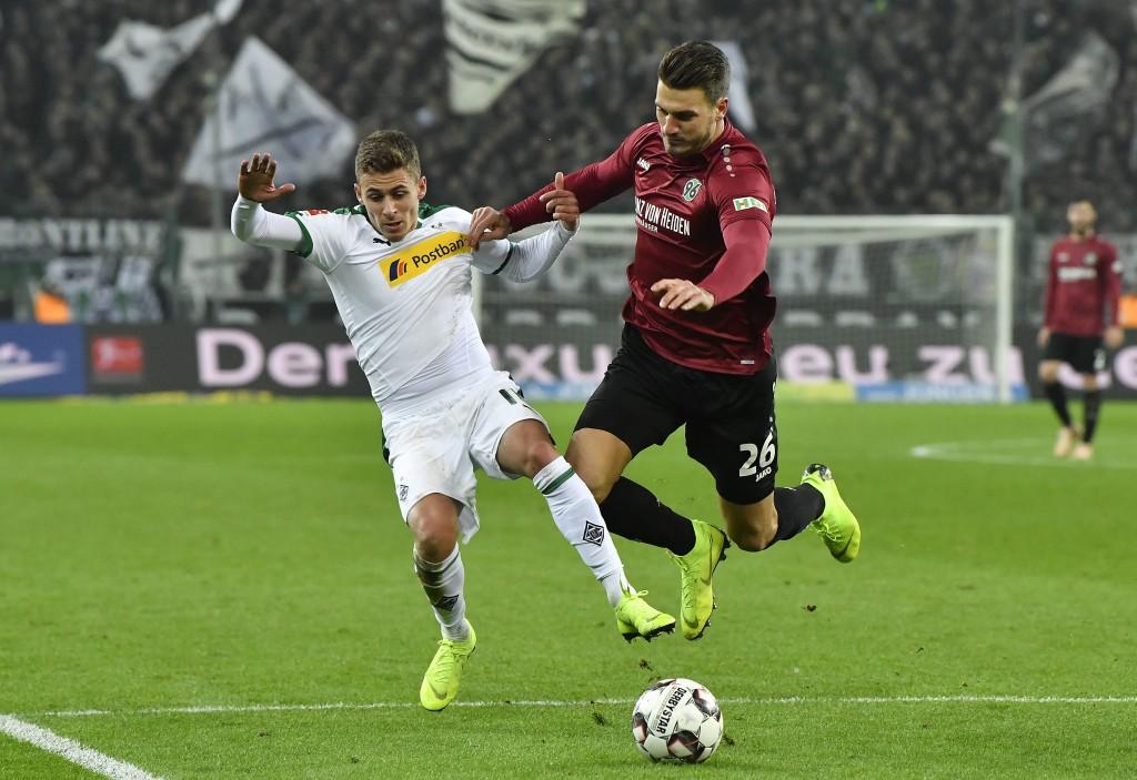 Moenchengladbach's Thorgan Hazard, left, and Hannover's Hendrik Weydandt challenge for the ball during the German Bundesliga soccer match between Boru