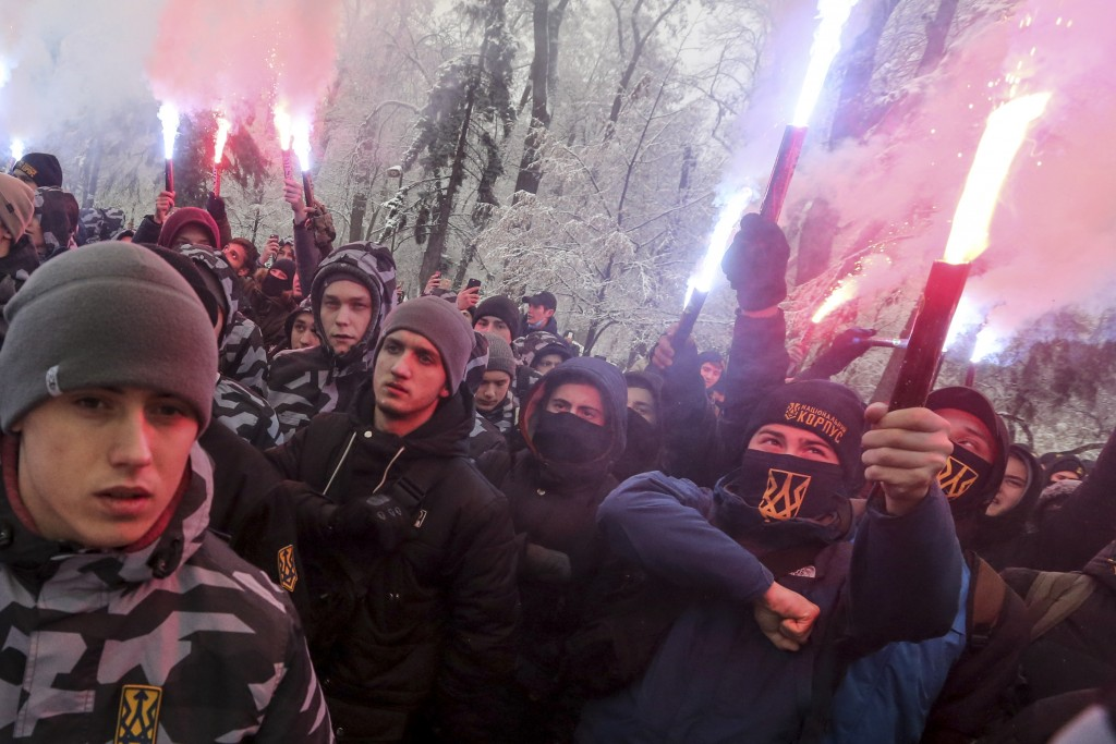 Volunteers with the right-wing paramilitary Azov National Corps hold flares during a rally on the snowy streets in front of the Ukrainian parliament i
