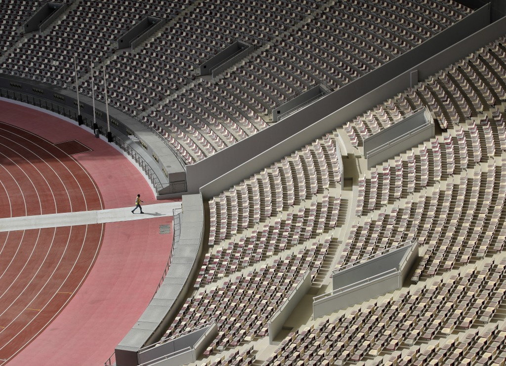 In this Wednesday, Oct. 31, 2018 picture a worker walks inside the Khalifa International Stadium in Doha, Qatar. Eight stadiums scattered in a 30-mile
