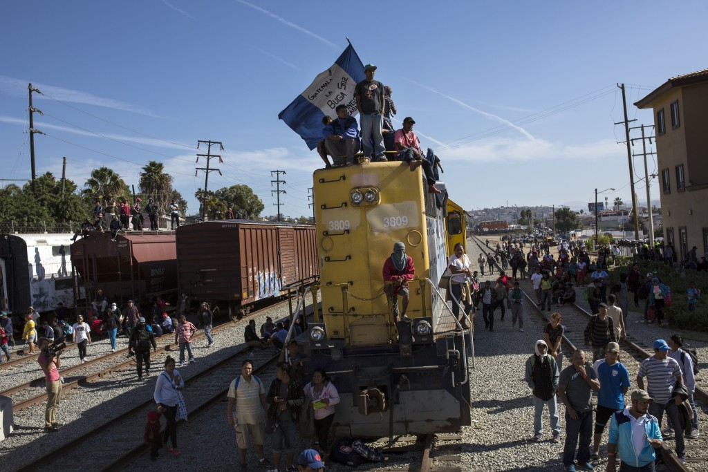 A migrant waves an Honduran flag along the railroad tracks at the Mexico-U.S. border in Tijuana, Mexico, Sunday, Nov. 25, 2018, as a group of migrants