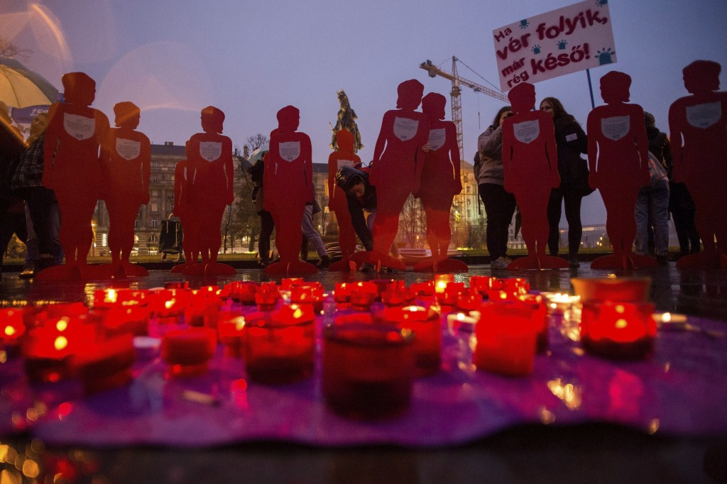Candles burn and female silhouettes are placed during a rally to mark the International Day for the Elimination of Violence Against Women,  outside th...