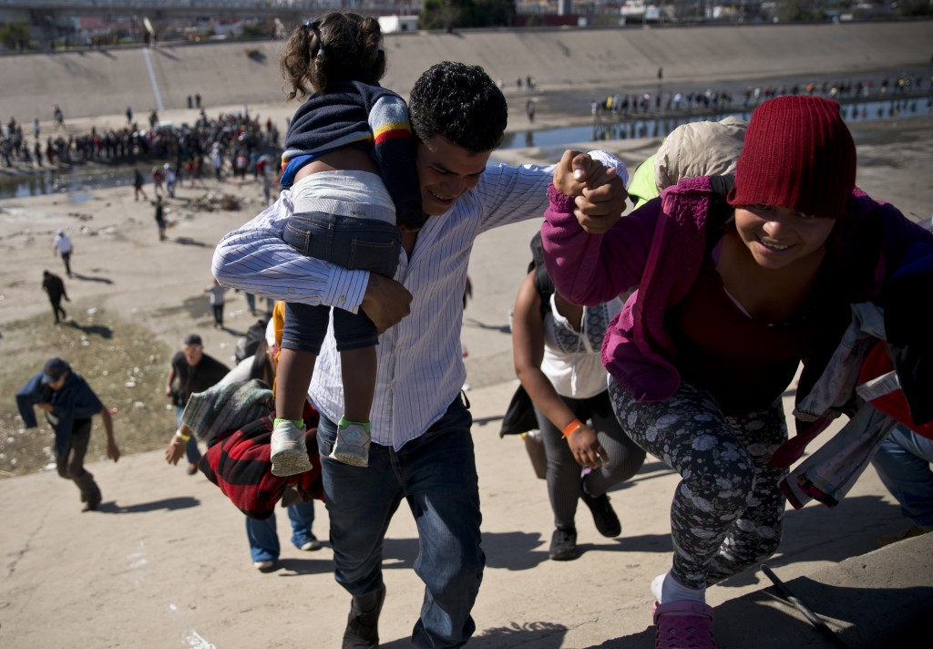 Migrants walk up a riverbank at the Mexico-U.S. border after getting past a line of Mexican police at the Chaparral border crossing in Tijuana, Mexico...