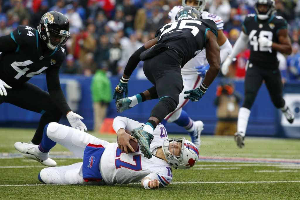 Buffalo Bills quarterback Josh Allen, bottom, slides as Jacksonville Jaguars defensive back D.J. Hayden (25) tries to avoid hitting him during the fir
