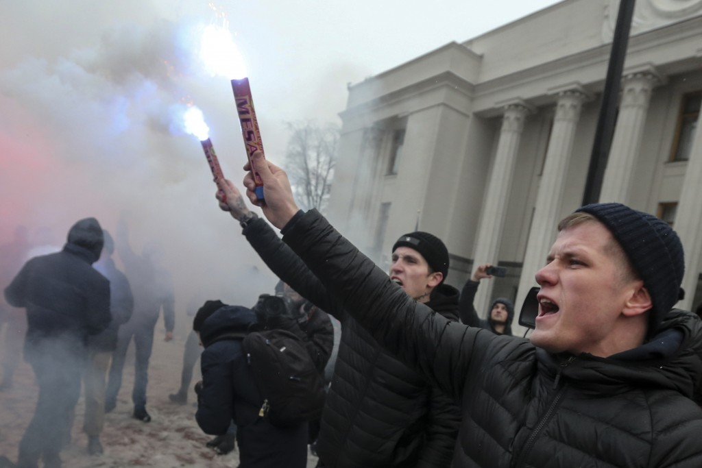 Volunteers with the right-wing paramilitary Azov National Corps light flares during a rally on the snowy streets in front of the Ukrainian parliament