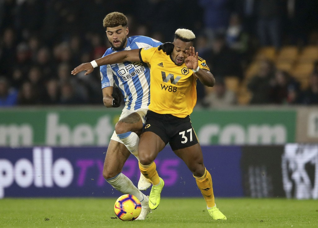 Huddersfield Town's Philip Billing, left, and Wolverhampton Wanderers' Adama Traore during their English Premier League soccer match at Molineux in Wo...