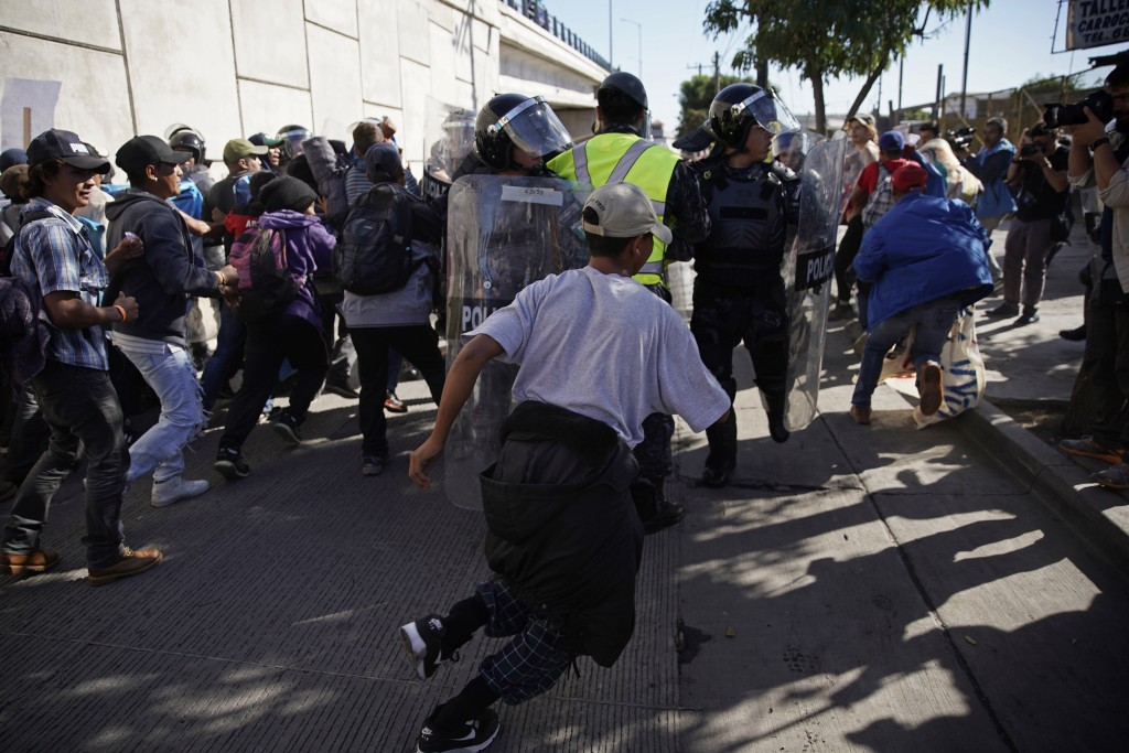 Migrants break past a line of police as they run toward the Chaparral border crossing in Tijuana, Mexico, Sunday, Nov. 25, 2018, near the San Ysidro e...