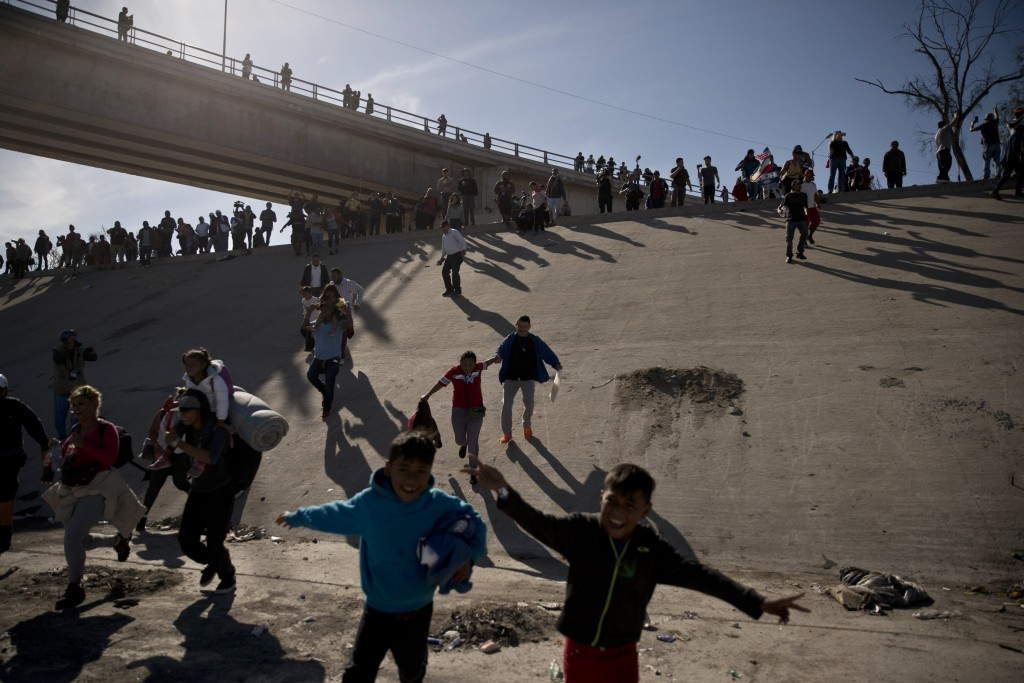 Migrants cross the river at the Mexico-U.S. border after pushing past a line of Mexican police at the Chaparral crossing in Tijuana, Mexico, Sunday, N...