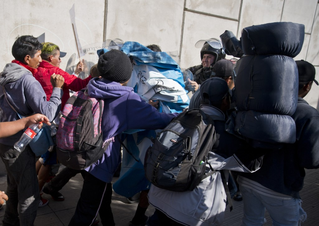Migrants push past Mexican police at the Chaparral border crossing in Tijuana, Mexico, Sunday, Nov. 25, 2018, as they try to reach the United States. ...