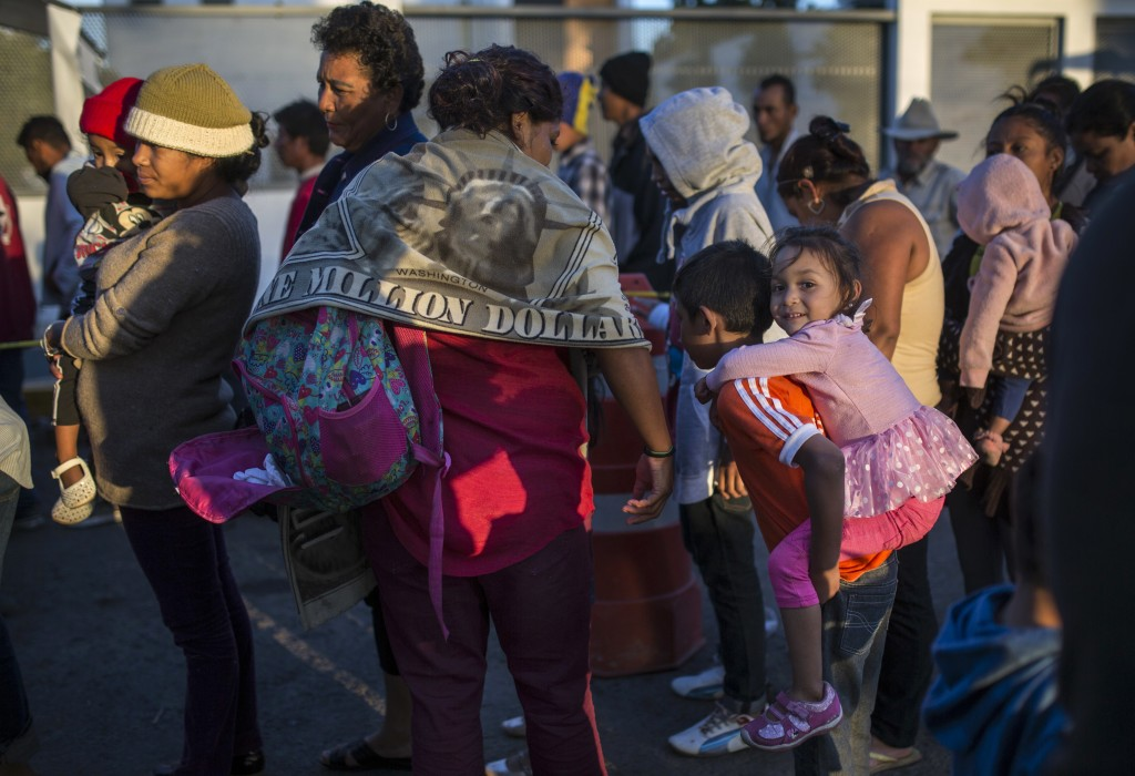 Migrants stand in a line waiting for donated food in Tijuana, Mexico, Sunday, Nov. 25, 2018, as they try to reach the U.S. The mayor of Tijuana has de