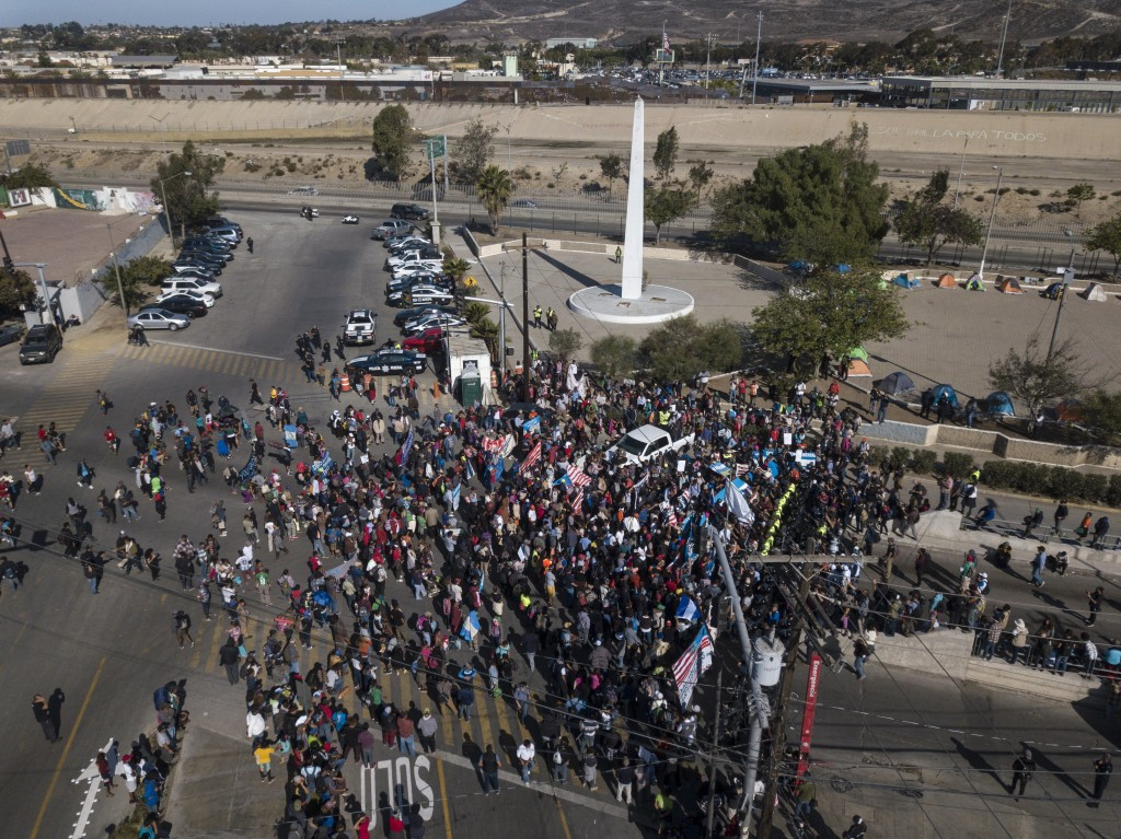 A group of migrants gather at the Chaparral border crossing in Tijuana, Mexico, Sunday, Nov. 25, 2018, as they try to pressure their way into the U.S.