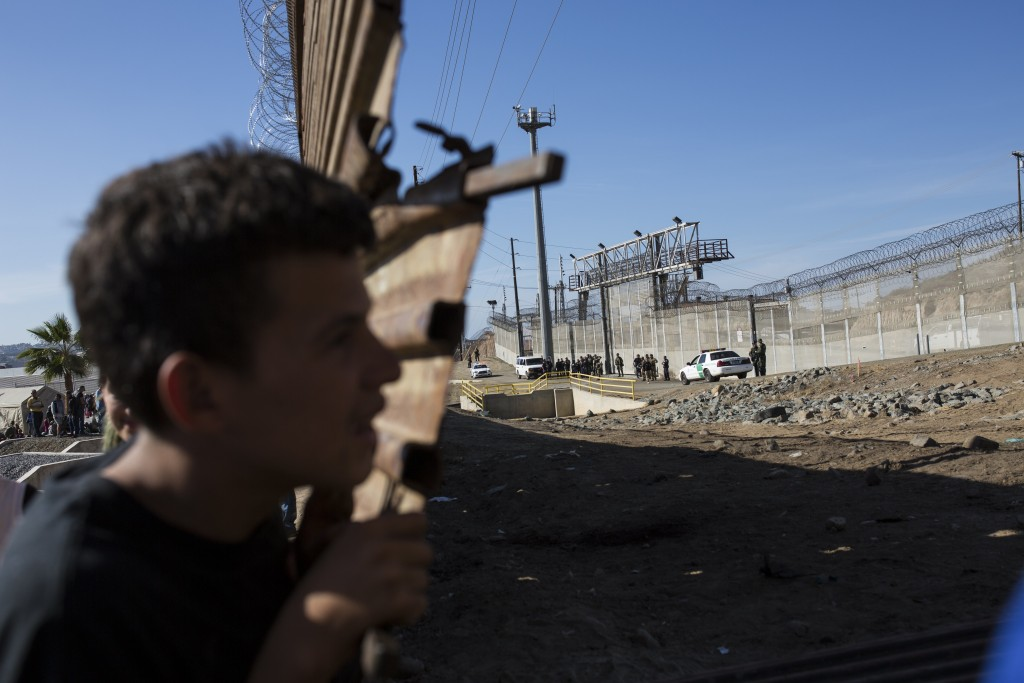 Migrants gather at the Mexico-U.S. border as U.S. agents stand guard, right, after the group pushed past Mexican police at the Chaparral crossing as t...