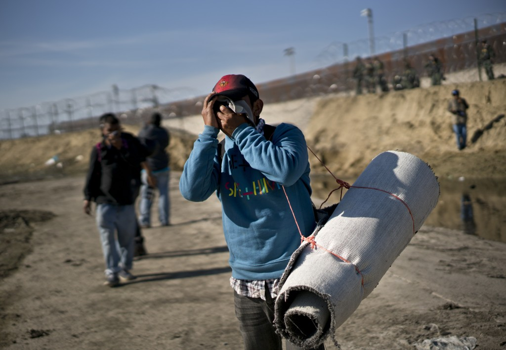 A migrant carrying a roll of carpet wipes his face after U.S. border agents fired tear gas at a group of migrants who had pushed past Mexican police a