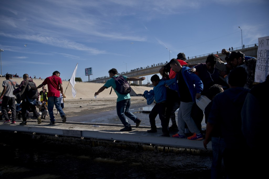 Migrants cross the river at the Mexico-U.S. border after getting past a line of Mexican police at the Chaparral crossing in Tijuana, Mexico, Sunday, N...