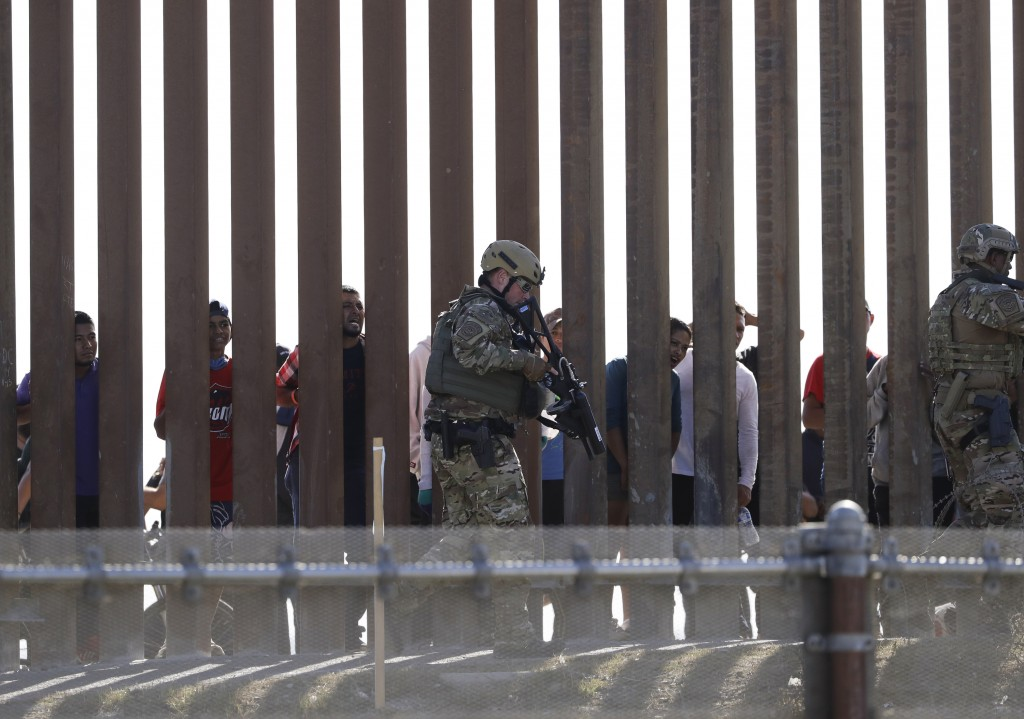 U.S. Customs and Border Protection officers walks along a wall at the border between Mexico and the United States, as seen from San Diego on Sunday, N...