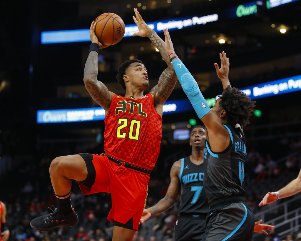 Atlanta Hawks forward John Collins (20) shoots as Charlotte Hornets guard Devonte' Graham (4) defends in the first half of an NBA basketball game on S...